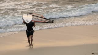 MS PAN Man walking up beach carrying windsurfing board