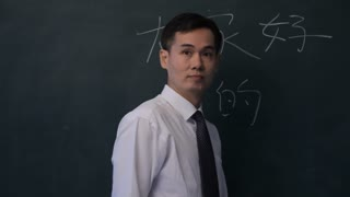 MS PAN Man writing Chinese characters on blackboard, turning to look at camera