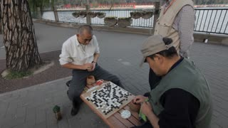 MS PAN Men playing traditional board game on bench in park / Beijing, China