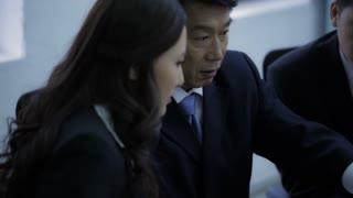 MS PAN TD TU Business people talking while using laptop / China