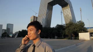 MS PAN Young man walking and talking on mobile phone, CCTV Headquarters building in background / Beijing, China