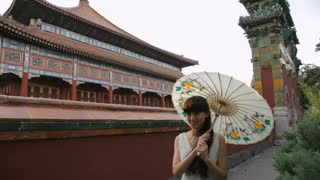 MS PAN Young woman with umbrella walking along Chinese temple's wall / Beijing, China