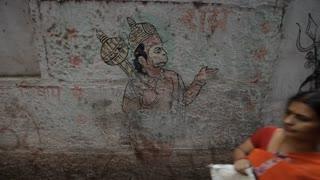 MS People walking by painting of Hindu Monkey God / Varanasi, India