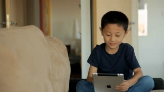 MS Portrait of boy playing on digital tablet on sofa / China