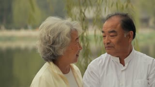MS Portrait of elderly couple talking and smiling together outdoors / China