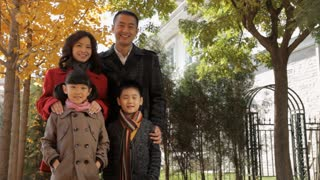 MS Portrait of family of four standing in park / China
