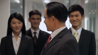 MS Portrait of senior businessman with colleagues standing in hallway / China
