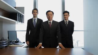 MS Portrait of three businessman standing behind desk / China