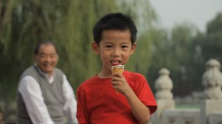 MS Portrait of young boy eating ice cream cone in park, grandfather looking on in background / China