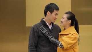 MS Portrait of young couple smiling standing by yellow wall/ China