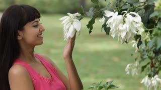 MS Portrait of young woman smelling blossoming flowers on tree / Singapore
