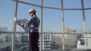 MS SELECTIVE FOCUS Architect with safety helmet stands in office with building plans in his hand / Singapore