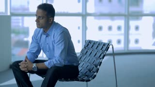 MS SELECTIVE FOCUS Businessman sits with hands clasped in empty office / Singapore
