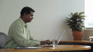 MS SELECTIVE FOCUS Businessman types on laptop in his office / Singapore