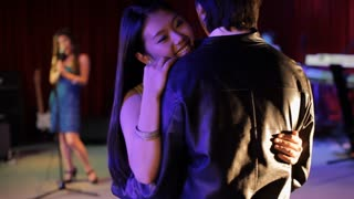 MS SELECTIVE FOCUS Couple slow dancing in night club, woman singing in background / China
