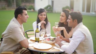 MS SELECTIVE FOCUS Couples talking during dinner in backyard / India