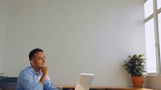 MS SELECTIVE FOCUS Man sits at his office desk staring at ceiling / Singapore