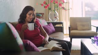 MS SELECTIVE FOCUS Mid-adult woman drinking coffee and reading book / India