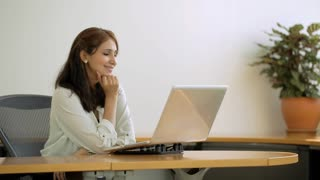 MS SELECTIVE FOCUS PAN Businesswoman sits at desk with hand on her chin, thinking / Singapore
