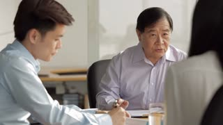 MS SELECTIVE FOCUS Senior businessman in discussion with two colleagues at meeting table / Singapore