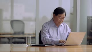 MS SELECTIVE FOCUS Senior businessman looks up from laptop and puts hand under chin / Singapore