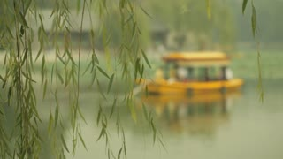 MS SELECTIVE FOCUS Tour boat floating on lake, willow tree in foreground / Beijing, China