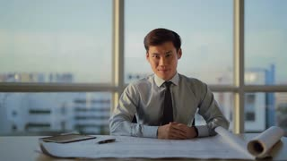 MS SELECTIVE FOCUS Young architect looks over building plans on his desk / Singapore