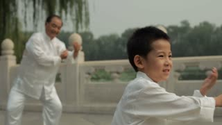 MS SELECTIVE FOCUS Young boy and mature man doing Tai Chi in a park by lake / Beijing, China