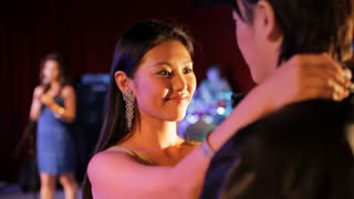MS SELECTIVE FOCUS Young couple slow dancing with woman singing in background in night club / China