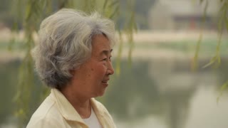 MS Senior woman looking at camera and smiling by the lake / China