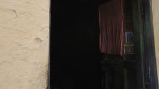 MS TD Man sitting in doorway reading newspaper / India