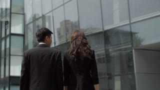 MS TD Rear view of businessman and businesswoman walking towards office building / Beijing, China