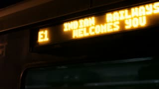 MS TD Train station sign with passengers in train / India