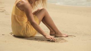 MS TU Blonde woman sitting on beach, drawing in sand