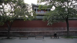 MS TU Elderly woman sitting in front of red wall / Beijing, China