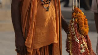 MS TU Indian Sadhu holding flower offerings / Varanasi, India