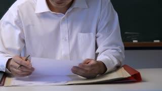 MS TU Man reading at desk, looking at camera, smiling