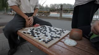 MS TU TD Men playing traditional board game on park bench / Beijing, China