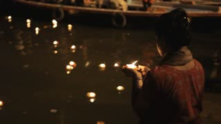 MS TU TD Woman putting offerings into Ganges river / Varanasi, India