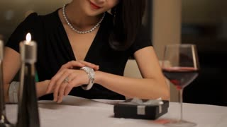 MS TU Woman looking at her diamond bracelet and smiling, sitting at dining table / China.