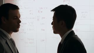 MS Two businessmen discussing in front of white board / China