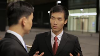 MS Two businessmen talking on street at night / China