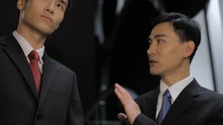 MS Two businessmen talking to each other moving down on escalator / China