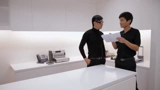 MS Two man talking by table in office / China