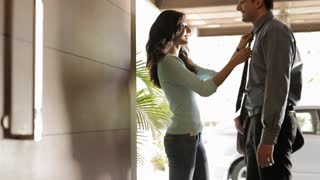 MS Woman adjusting boyfriend's necktie at doorway / India