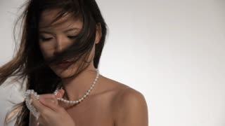 MS Woman holding pearl necklace with hair blowing in wind