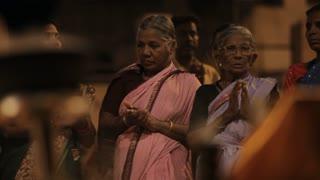 MS Women wearing saris and clapping, incense burning in foreground / Varanasi, India