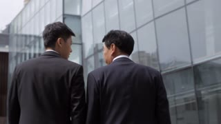 MS WS TD Two businessmen walking towards office building/ Beijing, China