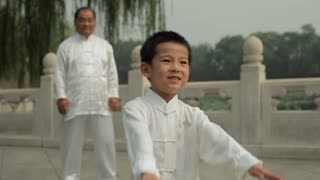 MS Young boy and mature man doing Tai Chi in a park/ Beijing, China