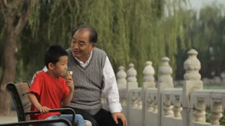 MS Young boy eating ice cream cone, sitting with his grandfather on park bench / China